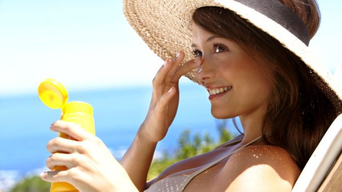 девушка мажется кремом от солнца